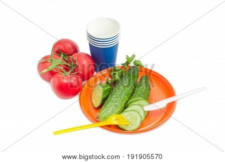 Disposable plastic plate whole and sliced cucumber with fork and knife on it cluster of the tomatoes blue paper disposable cups beside on a light background