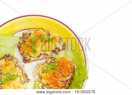 Fragment of the dish with several pork chops baked with onion mushrooms and cheese and decorated with parsley and lettuce leaves on a light background