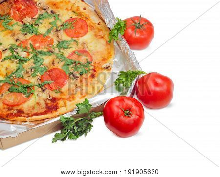 Fragment of the cooked round pizza with tomatoes mushrooms and arugula wrapped in aluminum foil in the open cardboard box and three fresh tomatoes beside on a light background
