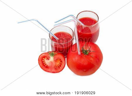 Big fresh whole tomato with bendable drinking straw inserted into it half of the tomato and two different glasses with tomato juice and drinking straws on a light background