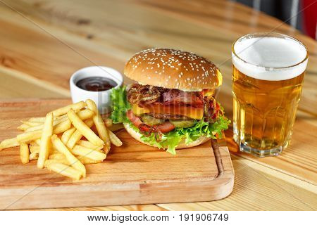Big tasty burger and fries with beer on background on the wooden table. fried bacon and onion rings. Lettuce and slices of tomato