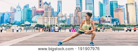 Running runner woman stretching legs in urban city banner panorama crop. Active lifestyle fitness girl doing leg stretches after workout on famous Bund boardwalk with skyline in Shanghai, China.