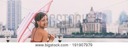 Chinese umbrella woman in rain background banner. Urban landscape panorama of Shanghai city Bund, Pudong Huangpu district, rainy summer day. Tourist traveling in Shanghai, China, Asia travel.