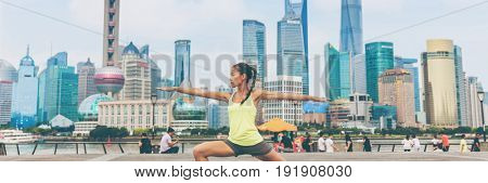 Fitness woman doing yoga in Shanghai city banner. Health and wellness copy space background. Panorama crop of Asia skyline urban background girl training warrior pose II workout class on the Bund.