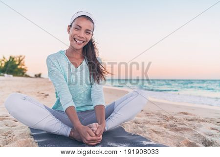 Yoga fitness beach woman stretching legs laughing. Happy Asian girl smiling during morning health workout. healthy active lifestyle.