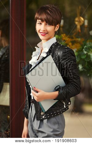 Happy young business woman with a folders walking in city street. Stylish fashion model in black leather jacket
