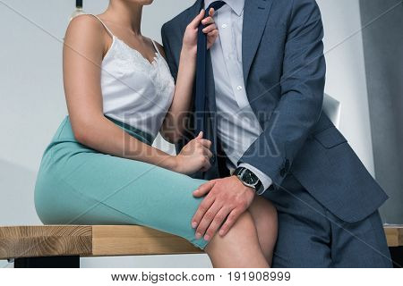Cropped shot of sensual businesswoman sitting on table and holding tie of male colleague