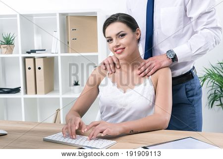 Young Businessman Touching Shoulders Of His Pretty Colleague At Workplace