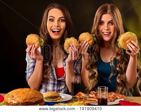 Hamburger fast food with ham and group people. Good Fast food concept. Friends two women eating sandwich junk in party. Girls fool around. Loving couple of lesbians are having supper in a cafe.