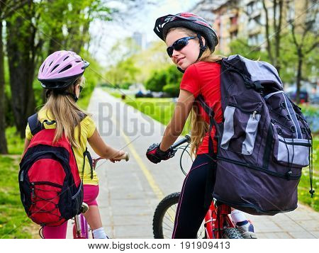 Bicycle path with children. Girls wearing helmet with rucksack ciclyng ride. Kids or mother with daughter are on yellow bike lane. Asphalt road goes into distance. Child travels unaccompanied.
