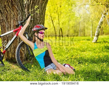 Girl traveling bicycle in summer park. Bicyclist has rest near bike. Cycling is good for health in summer and spring. Girl is waiting for guy on date. Happy resting teenager.