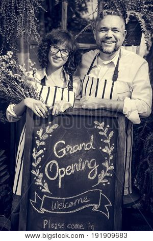 Adult Man and Woman Standing with Grand Opening Sign