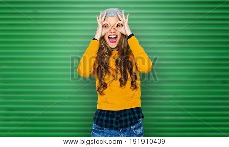 people, style and fashion concept - happy young woman or teen girl in casual clothes and hipster hat having fun over green ribbed wall background