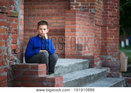 Boy Teenager Sitting On Porch At Home