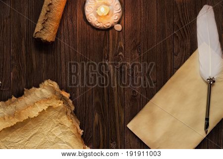 Old Blank Scroll Paper And Quill On Wooden Table Illuminated By  Candle