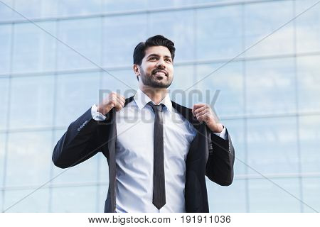Arabic serious smiling happy successful positive businessman or worker in black suit with beard standing in front of an office glass building and straightening his jacket with his hands.