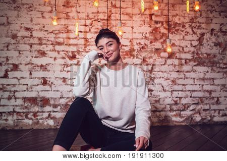 Attractive brunette in gray sweatshirt sits on brick wall background. Mock-up.