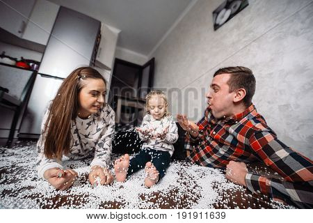 Dad mom and little daughter play together on the floor in a room with polystyrene balls