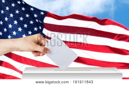 voting, civil rights and people concept - male hand putting his vote into ballot box on election over american flag background