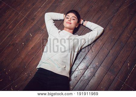 Attractive brunette in a gray sweatshirt lies on a wooden floor. Mock-up.