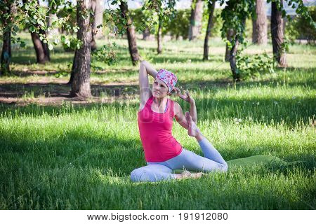 young woman doing yoga and gymnastics in the Park. Yoga in the Park, outdoors , women's health, Yoga woman. The concept of healthy lifestyle and recreation.