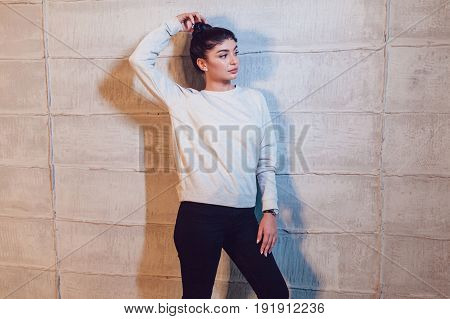Attractive brunette in a gray sweatshirt on a light background. Mock-up.