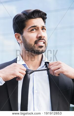 Arabic serious angry irritated businessman or worker in black suit with beard standing in front of an office building and taking his tie off with his hands.