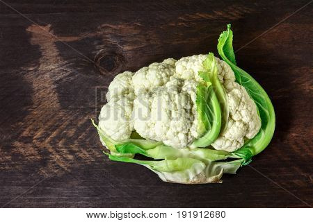 An overhead photo of a half of a cauliflower, with elegant curving green leaves, on a dark rustic background with a place for text