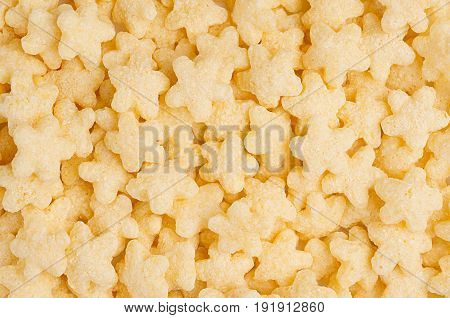Yellow stars corn flakes closeup background cereals texture. Top view.
