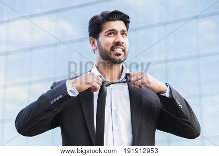 Arabic serious angry irritated businessman or worker in black suit with beard standing in front of an office glass building and taking his tie off with his hands.
