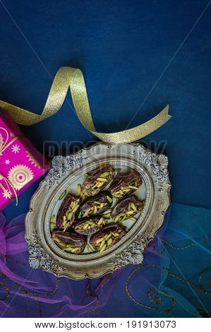 Finest quality dates stuffed with pistachio nuts served on a vintage plate. An exotic arabian date fruits and gifts for happy moments.