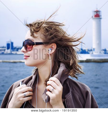 portrait of beautiful happy girl listening music at the seaside