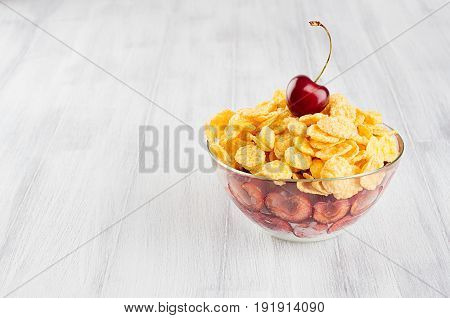 Healthy breakfast in bowl with golden corn flakes decorated cherry on white wood board. Decorative border with copy space.