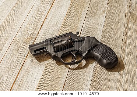 Loaded Black Revolver On A Wood Table