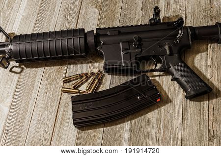 AR-15 rifle chambered in 5.56 nato lying on a wooden table
