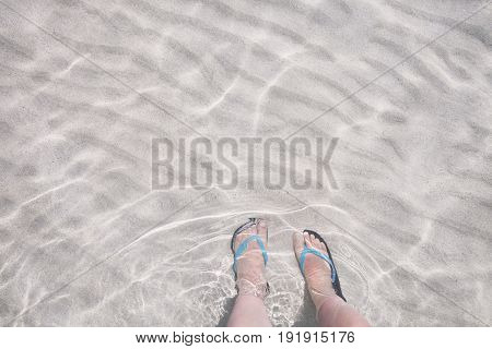 Feet in flip flops in transparent sea water on a white sandy bottom. Summer vacation travel
