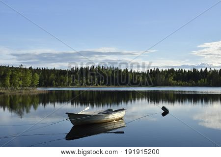 Boat moored on a calm lake with forest and blue sky in background picture from the North of Sweden.