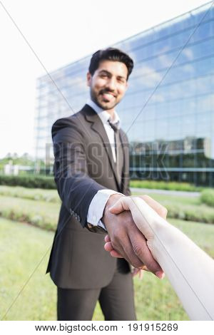 Arabic serious smiling happy successful positive businessman or worker in black suit with beard standing in front of an office glass building and shaking hands with a person.