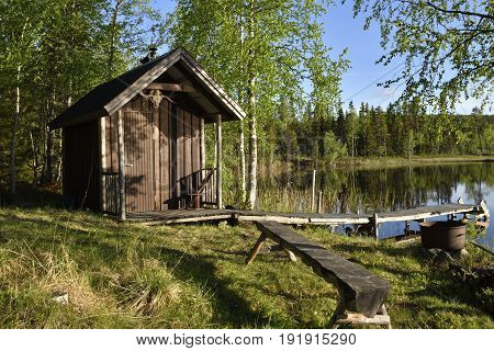 Little fishing cottage att the lake shore surrounded by birch trees with a wooden handmade bench in foreground and with a jetty down to the lake picture from the North of Sweden.