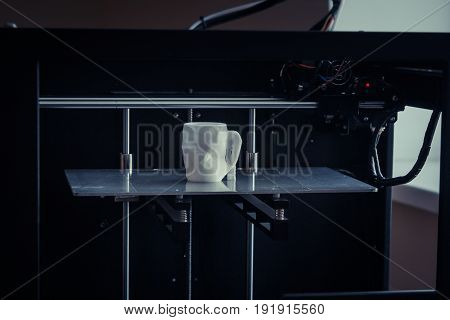 Objects printed by 3d printer. Dark filter. Copy spase. Automatic three dimensional 3d printer performs plastic modeling in laboratory. Progressive modern additive technology