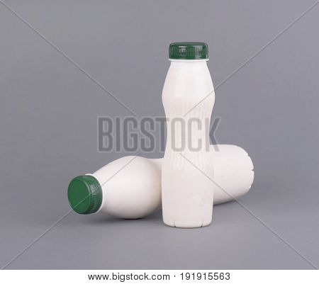 White plastic bottle with milk, yogurt or kefir, on a gray background. Mock up template design without label. Photo