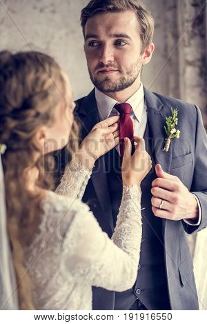 The bride take care of groom tie for wedding