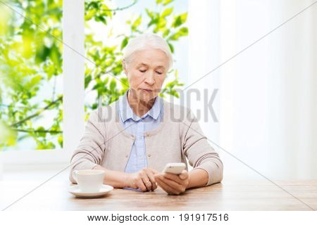 technology, communication age and people concept - senior woman with smartphone and coffee sitting at table and texting message at home over green natural background