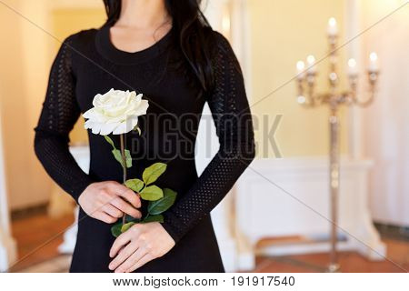 people and mourning concept - woman with white rose at funeral in church