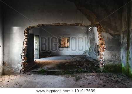 Damaged building interior with large hole in the wall
