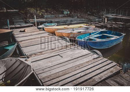 Wooden old berth. Dark filter. There are several boats on the dock. Sunny warm day. Copy spase.