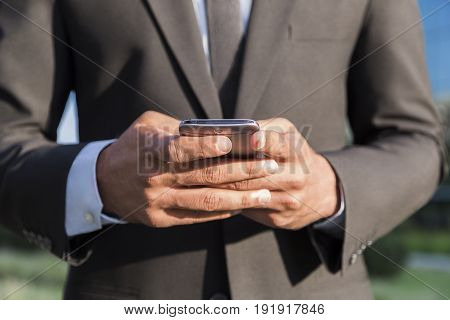 Anonymous unknown businessman or worker in black suit standing in front of an office glass building and holding a smartphone in his hand.