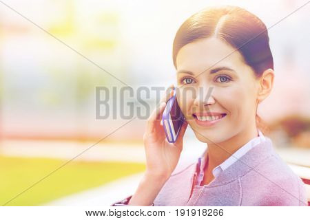 business and people concept - young smiling businesswoman calling on smartphone in city