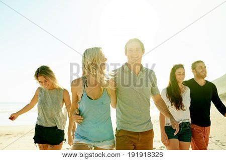 Carefree Group Of Friends Walking Together Down A Sandy Beach