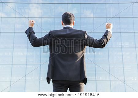 Successful happy businessman or worker in black suit standing in front of an office glass building with raised hands celebrating victory.